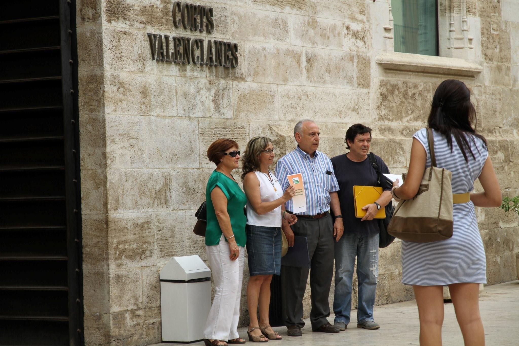 Maria Nuñez, de la Intersindical Valenciana, amb altres persones de l'Aliança en la porta de les Corts Valencianes.